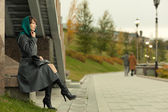 Beautiful stylish woman in grey coat sitting outdoors — Stock Photo