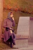 Beautiful stylish woman in coat sitting outdoors — Stock Photo