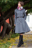 Picture of smiling young woman in grey coat walking at park — Stock Photo