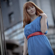 Beautiful woman in blue dress and red belt — Stock Photo