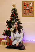 Happy woman with gifts near christmas tree — Стоковое фото