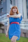 Beautiful woman in blue dress and red belt outdoors — Stock Photo