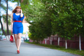 Beautiful woman in blue dress outdoors — Стоковое фото