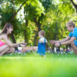 Happy parents with a baby in a greenl summer park — Stock Photo