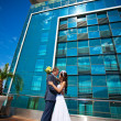 Bride and groom is kissing near the blue glass modern building — Stock fotografie