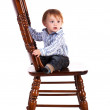 Baby on a big wooden chair in a studio. isolated — Stock Photo
