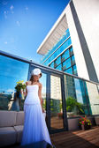 Beautiful bride on modern building background — Stock Photo