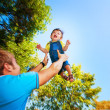 Happy daddy is throwing baby in a greenl summer park — Stock Photo