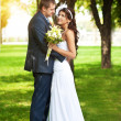 Stock Photo: Happy bride and groom in a greenl summer park