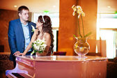 Happy bride and groom next to the piano — Stock Photo