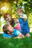 Happy family are walking in the green summer park — Stock Photo