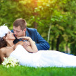 Bride and groom are lying on green grass — Stock Photo