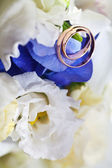 Wedding bouquet and gold rings — Stock Photo