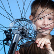Stock Photo: Boy is repairing the bicycle wheel