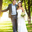 Happy bride and groom in a greenl summer park — Stock Photo #13627579