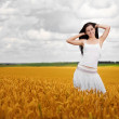 Cute women is walking in wheat field — Stock Photo