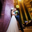 Happy bride and groom in modern hotel hall — Stock Photo #13627815