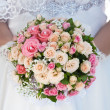 Bouquet of pink roses in the bride's hands — Stock Photo