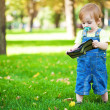 Baby playing with a purse in the green park — Stock Photo #13815500
