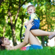 Funny baby with mom in a greenl summer park — Stock Photo #13815572
