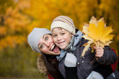 Mom and son on a yellow autumn park background — Stock Photo