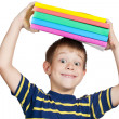 Stock Photo: Boy with a stack of books on his head. isolated