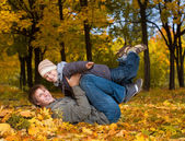 Happy dad and son in a yellow autumn park — Стоковое фото