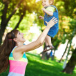 Happy mom is throwing baby in a greenl summer park — Stock Photo