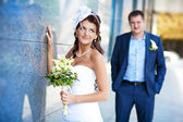 Bride and groom is standing near the granite wall — Stock Photo