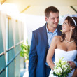 Bride and groom are hugging near the glass wall — Stock Photo #14076082