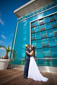 Bride and groom is kissing near the building — Stock Photo
