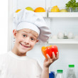 Stock Photo: Cute scullion is choosing food near open refrigerator