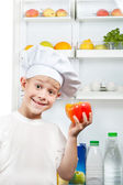 Cute scullion is choosing food near the open refrigerator — Stock Photo