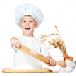 Stock Photo: Funny little scullion is kneading dough
