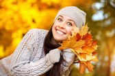 Happy cheerful woman on a background of autumn trees — Stock Photo