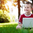 Boy sitting with a laptop on the grass — Stock Photo #14672081