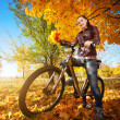Girl with bike on a autumn leafs background — Stock Photo