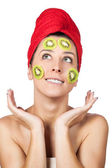 Beautiful woman with kiwi fruit mask over white background — Stock Photo