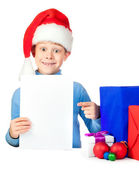 Happy boy with a sheet of paper and lot of Christmas gifts — Stock Photo