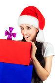Noel baba şapkası pek çok hediye ile mutlu bir kadın — Stok fotoğraf