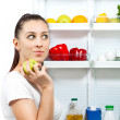 Cute girl is choosing food near the open refrigerator — Stock Photo