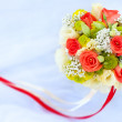Bouquet of rad roses on the white wedding dress - Stock Photo