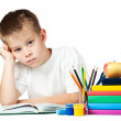 Stock Photo: Sad schoolboy is doing his homework