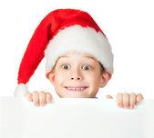 Funny boy in a rad Santa hat is hiding — Stock Photo
