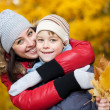 Stock Photo: Happy Mom and son are playing in yellow autumn