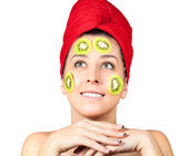 Attractive woman with kiwi fruit mask over white background — Stock Photo