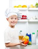 Cute cook boy is choosing food near the open refrigerator — Stock Photo