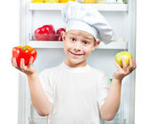 Cute smaster chef is choosing food near the open refrigerator — Stock Photo