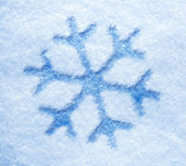 Blue snowflake on a snowy background — Stock Photo