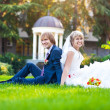 Happy couple are sitting on the green grass — Stock Photo
